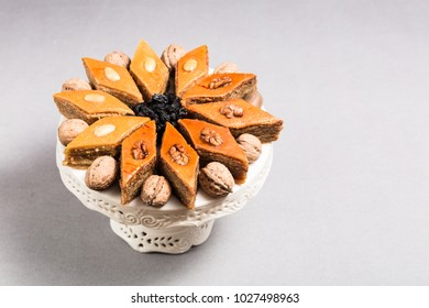 Traditional pakhlava baklava pastry from Azerbaijan made of walnuts and almonds with honey in round white plate cake stand on grey background, Novruz eastern new year spring celebration concept