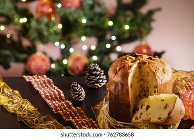 A traditional panettone, the famous italian Christmas cake on a wooden table. Blurred Christmas tree and decoration on background.