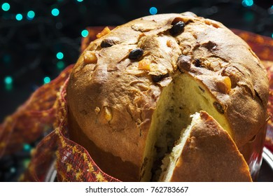 A traditional panettone, the famous italian Christmas cake. Blurred Christmas lights on background.