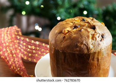 A traditional panettone, the famous italian Christmas cake. Blurred Christmas tree on background and decoration.