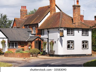 A traditional part whitewashed English Village Public House in Summer, with hanging flower baskets
