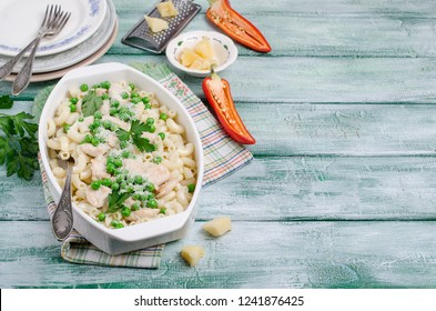 Traditional pasta with chicken slices, green peas and cheese on wooden background. Selective focus.