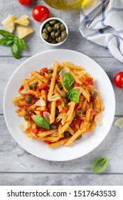 Traditional pasta putanesca with tomato sauce (capers, onions, garlic, anchovies). Delicious Italian food with Parmesan cheese, vegetarian Penne