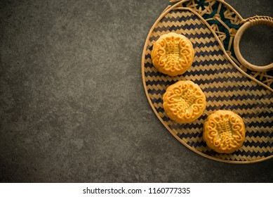 "Traditional pastry mooncakes is offered to friends or family during Mid-Autumn Festival. Flatlay table top view dark light with copy space. The Chinese character  represent ""lotus paste"""