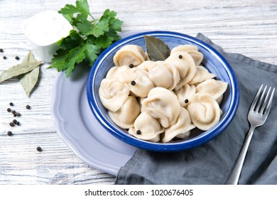 Traditional pelmeni, ravioli, dumplings filled with meat on wooden background, russian kitchen