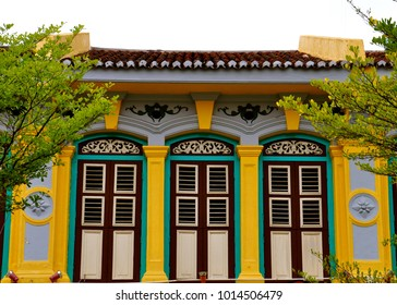 Traditional peranakan chinese shophouse which has been conserved and upgraded. Painted in bright colours of yellow, blue brown and green.