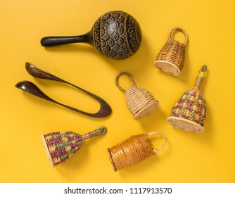 Traditional percussion musical instruments on yellow background. Caxixi shakers, maracas and musical spoons.