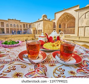 Traditional persian restaurant offers tasty tea with local sweets on the tray - candies of rock sugar and almond pancakes, Kashan, Iran.