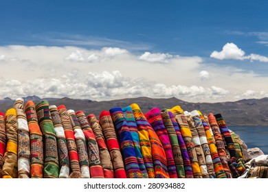 Traditional peruvian tissues and rug handmade in the andean plateau. Mountain and lake background with white clouds