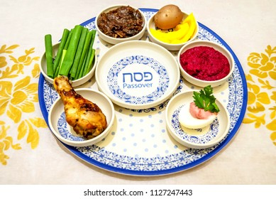 A traditional Pesach (Jewish Passover holiday) plate with the holiday name in Hebrew and English. Matzo and Pesach celebration concept. Passover seder plate.