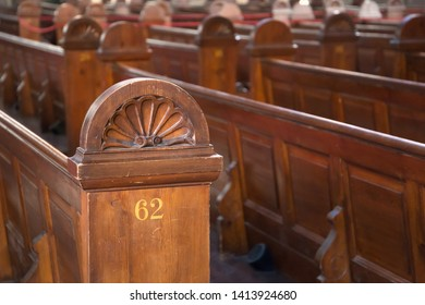 Traditional pews, made of carved wood and numbered, in an empty church.