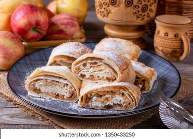 Traditional piece of apple strudel with powdered sugar in a plate on a table. horizontal