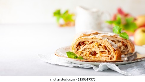 Traditional pieces of apple strudel with cinnamon,raisin, powdered sugar and mint.