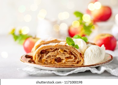 Traditional pieces of apple strudel with cinnamon,raisin, powdered sugar and  vanilla ice cream. Dessert for Christmas.