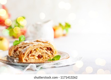 Traditional pieces of apple strudel with cinnamon,raisin, powdered sugar and mint. Dessert for Christmas.