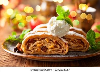 Traditional pieces of apple strudel with cinnamon,raisin, powdered sugar and  vanilla ice cream.
