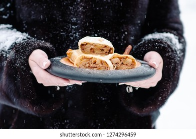 Traditional pieces of apple strudel with cinnamon,raisin, powdered sugar and vanilla ice cream. Woman in a fur coat holding a plate with strudel. Winter baking. Christmas baking.