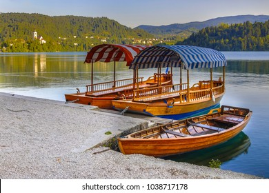 Traditional Pletna boats on beautiful lake Bled. In the background is the famous island with St Mary's church on a cliff. Slovenia, Europe