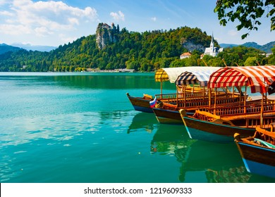 Traditional pletna boats on the green waters of Lake Bled with Bled Castle cliff on the background, Upper Carniola, Slovenia
