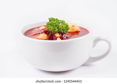 Traditional polish Christmas Eve dish: red borscht with uszka a mushroom filled kind of dumpling decorated with parsley