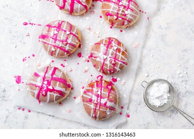Traditional Polish donuts with pink frosting and heart sprinkles on light background. Tasty doughnuts with jam.
