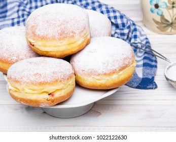 Traditional Polish donuts with powdered sugar on wooden background. Tasty doughnuts with jam.