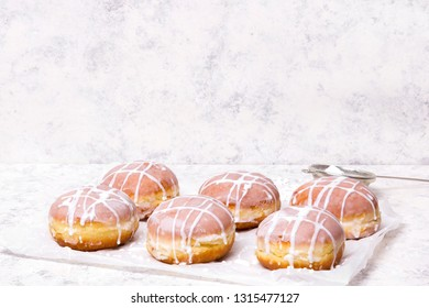 Traditional Polish donuts with white frosting on white background. Tasty doughnuts with jam.