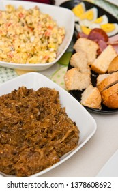 A traditional Polish Easter table setting with tasty foods and dishes. Bigos (cabbage) dish.