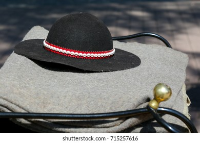 The traditional Polish highlander hat lies on a grey blanket. Such a hat is a part of highlander's outfit, but it is also often gift from a trip to Zakopane in Poland