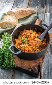 Traditional Polish kraut stew bigos with sausage, meat and mushrooms as closeup in a cast iron pot on an old wooden table