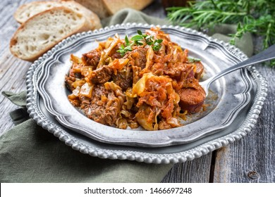 Traditional Polish kraut stew bigos with sausage, meat and mushrooms as closeup on a pewter plate on an old wooden table