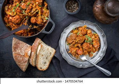 Traditional Polish kraut stew bigos with sausage, meat and mushrooms as top view in a cast iron pot and pewter plate on an old rustic board