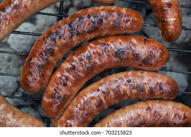 Traditional Polish sausages being prepared on a barbecue.