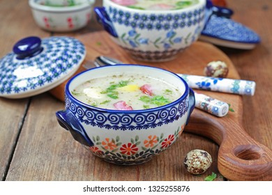 Traditional polish soup Zurek with potato, eggs and sausages in ceramic bowl, selective focus.