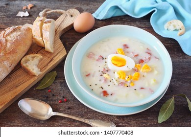 Traditional polish soup Zurek. Sour soup with sausage,  potatoes and eggs in ceramic bowl