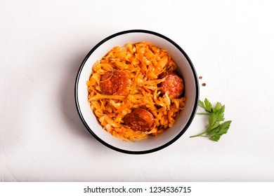 Traditional Polish stew of various kinds stewed with sauerkraut and shredded fresh cabbage. Typical food of Poland, Ukraine or Russia. Top view on the white background