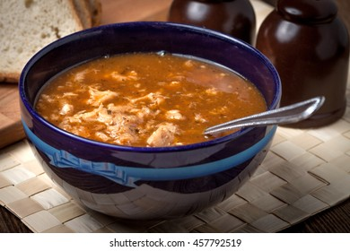 Traditional polish tripe soup with vegetables in blue bowl.