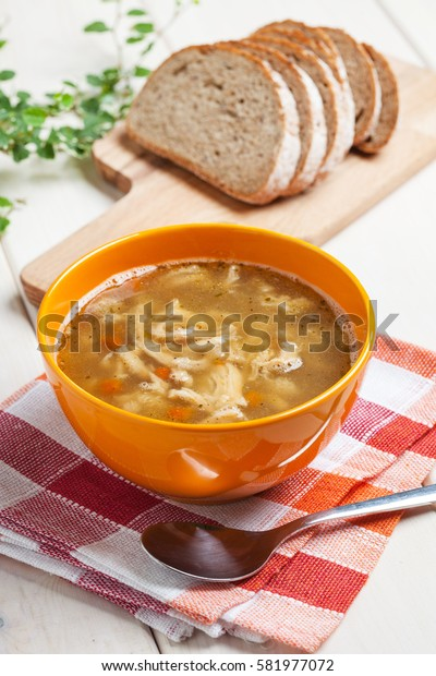Traditional polish tripe soup with vegetables in orange bowl.