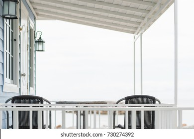 Traditional porch or portico deck interior- exterior space in front of vacation white blue beach house under the roof with a couple of cozy chair seats facing sea view on beachfront