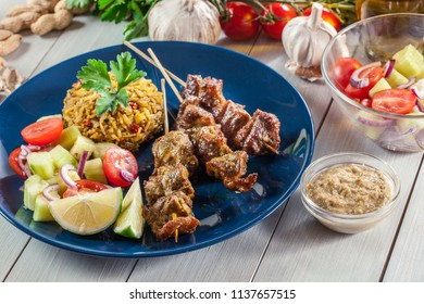 Traditional pork satay with peanut sauce and vegetables. Indonesian and Malaysian food.
