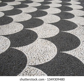 traditional portugal black and white fish scale pattern tiled cobblestone sidewalk in funchal madeira
