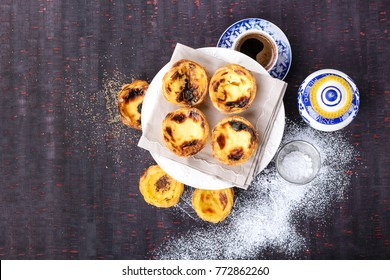 Traditional Portugese pastry Pastel de Nata served with coffee and honey on traditional tray over a rustic wooden board. Top View. Copy Space