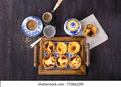 Traditional Portugese pastry Pastel de Nata served with coffee and honey on traditional tray over a rustic wooden board. Top View.