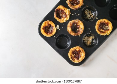 Traditional Portuguese egg tart dessert Pasteis Pastel de nata in black baking tray over white marble background. Flat lay, space