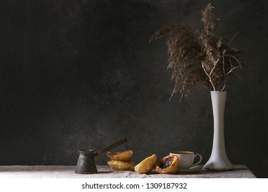 Traditional Portuguese egg tart dessert Pasteis Pastel de nata with cup of black coffee standing on linen table cloth near dark grey wall.