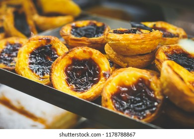 Traditional Portuguese egg tart pasty cakes, dessert Pasteis de nata with different portuguese pastry on the cafe store window, pastel de nata