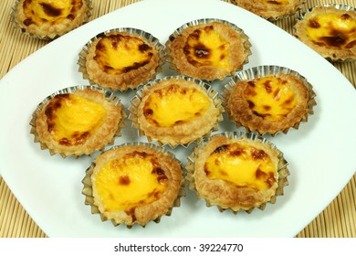 Traditional portuguese egg tarts - pastries pasteis de nata in tin moulds on white plate