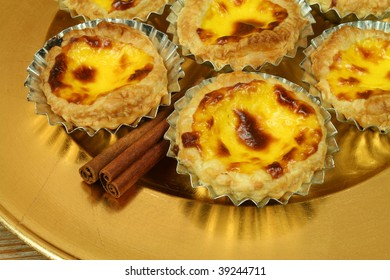 Traditional portuguese egg tarts - pastries pasteis de nata on golden plate with cinnamon sticks
