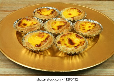 Traditional portuguese egg tarts - pastries pasteis de nata on golden plate