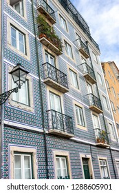 Traditional portuguese facade decoration azulejos. Blue and white azulejo tiles. Azulejo exterior with balconies and lantern in Lisbon, Portugal. Ceramic design of buliding. Architecture concept.